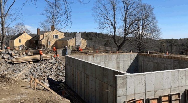 The dining commons concrete foundation will include a root cellar. The existing 18th century farmhouse (background) will be retrofitted in a later phase.